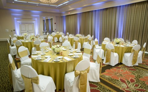 Airtel wedding reception tables in large banquet space, round tables fill the room with gold and white linens and accent lighting