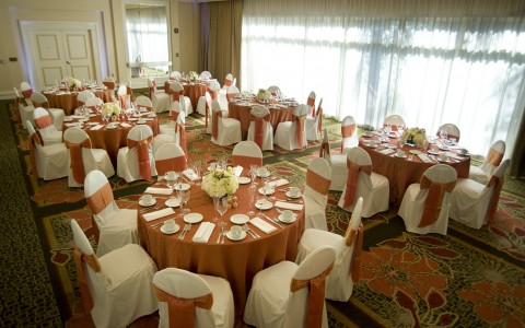 Airtel wedding reception tables with light pink linens and chairs draped in white