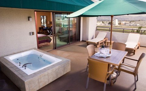 Outdoor Terrace Spa room sliding door leads out to ultra-spacious private balcony with jetted tub, chaise lounge and bistro dining table with umbrella.