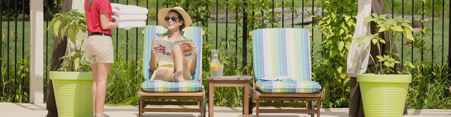 Photo of woman sitting beside the pool talking to worker with towels