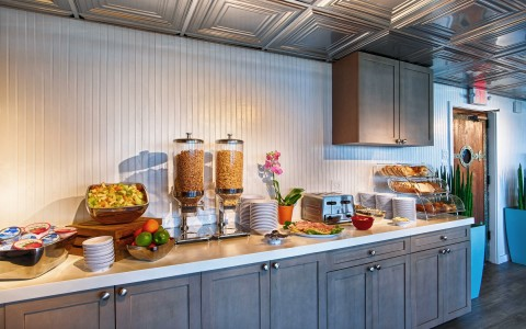 Counter filled with breakfast buffet including fruit, cereal, toast & pastries