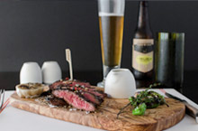 Steak on cutting board with glass of beer in the back