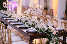 Long rectangular table set for wedding reception with floral centerpieces