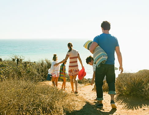 Family walking down trail surrounded by tall grass toward beach