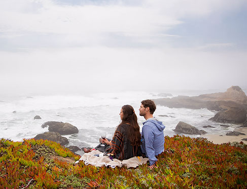 Couple sitting on grass by ocean looking off in the distance