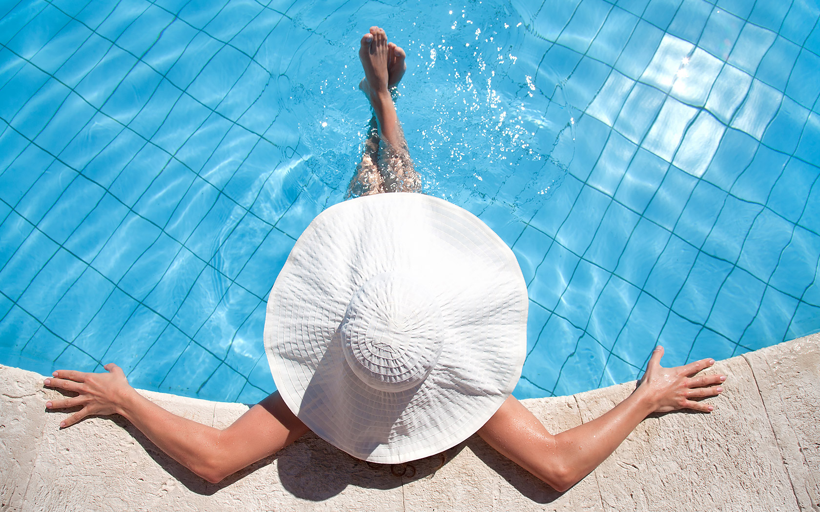 a woman in a white hat enjoying the pool