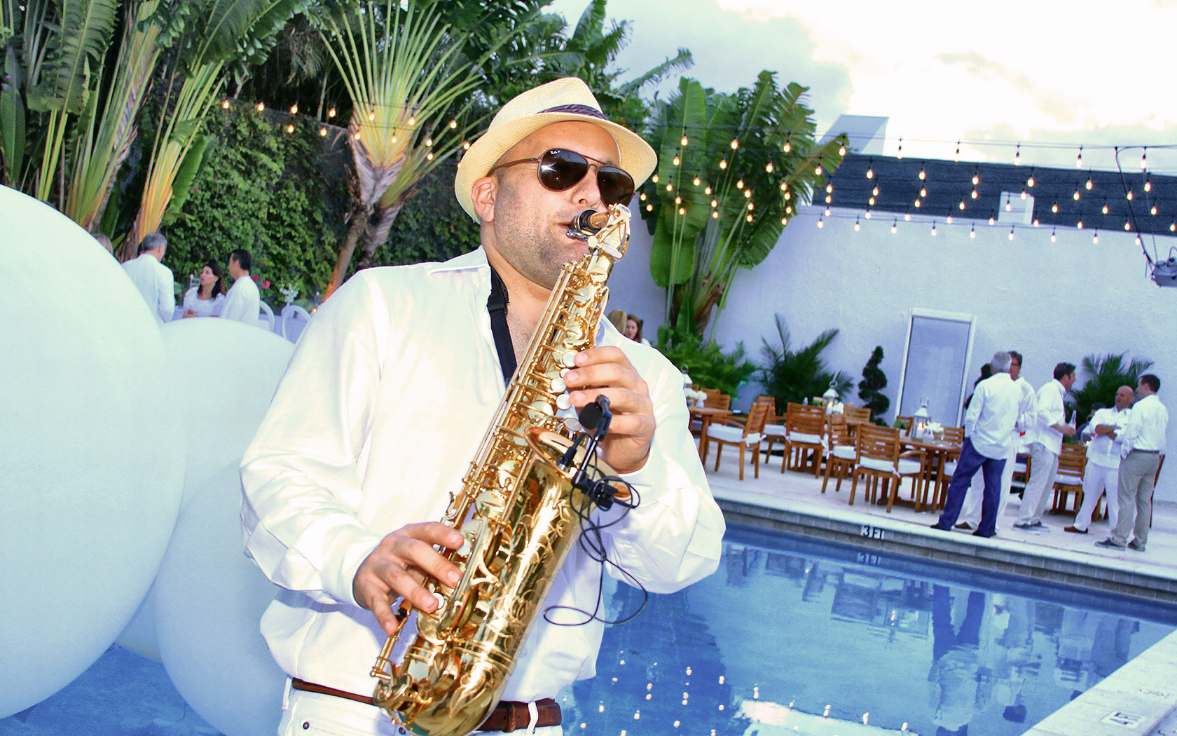 a man playing a saxophone by the pool