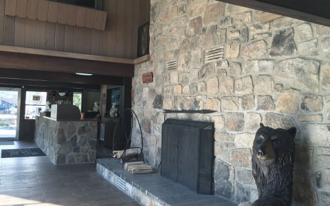 Lobby with stone walls, fireplace & bear sculpture