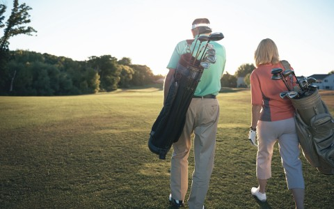 Couple walking with golf bags