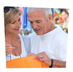 elder couple peeking into orange shopping bag
