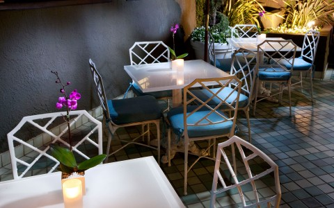 outdoor restaurant seating with candles and white square tables