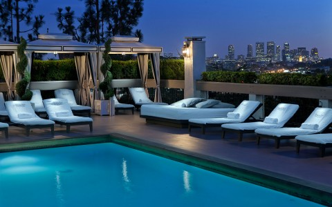 dusk pool view with cabanas and lounge chairs