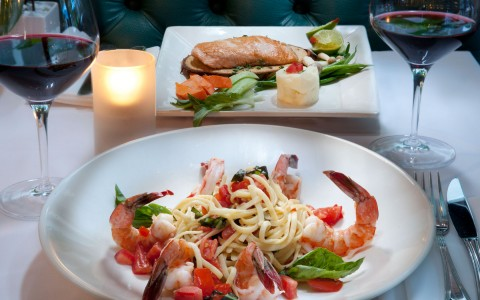 two seafood dishes on table with wine and candle