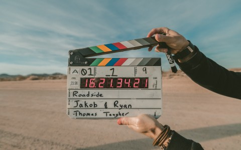 Pair of hands holding film clapperboard in front of desert setting