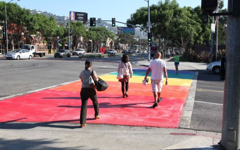pedestrians walk across rainbow colored street cross walk
