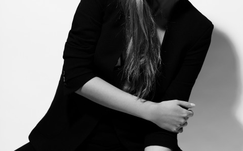 black and white photo of female model in black slacks and fitted jacket