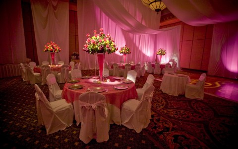 Tables & chairs set for event with pink decor & lighting