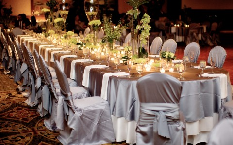 Long table set with fabric wrapped chairs & plant centerpieces