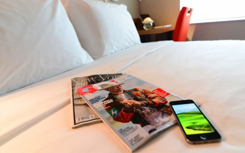 Two magazines and smartphone on hotel bed