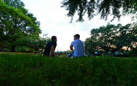 Two men talking on the grass