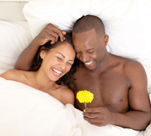 Couple in bed smiling