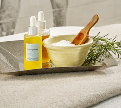 Two oil bottles & one bowl with salts on tray for spa