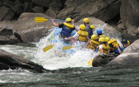 Nine people in blue and yellow whitewater rafting among large rocks