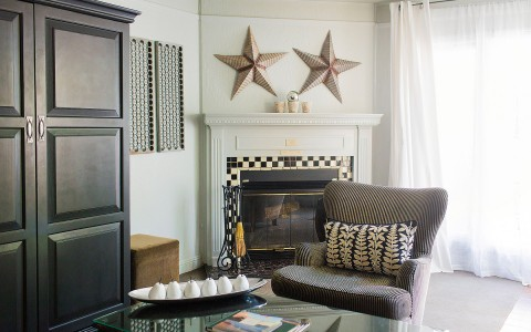 king cottage suite with fireplace and stars hanging over the mantle, accent chair with decorative pillow in front of coffee table