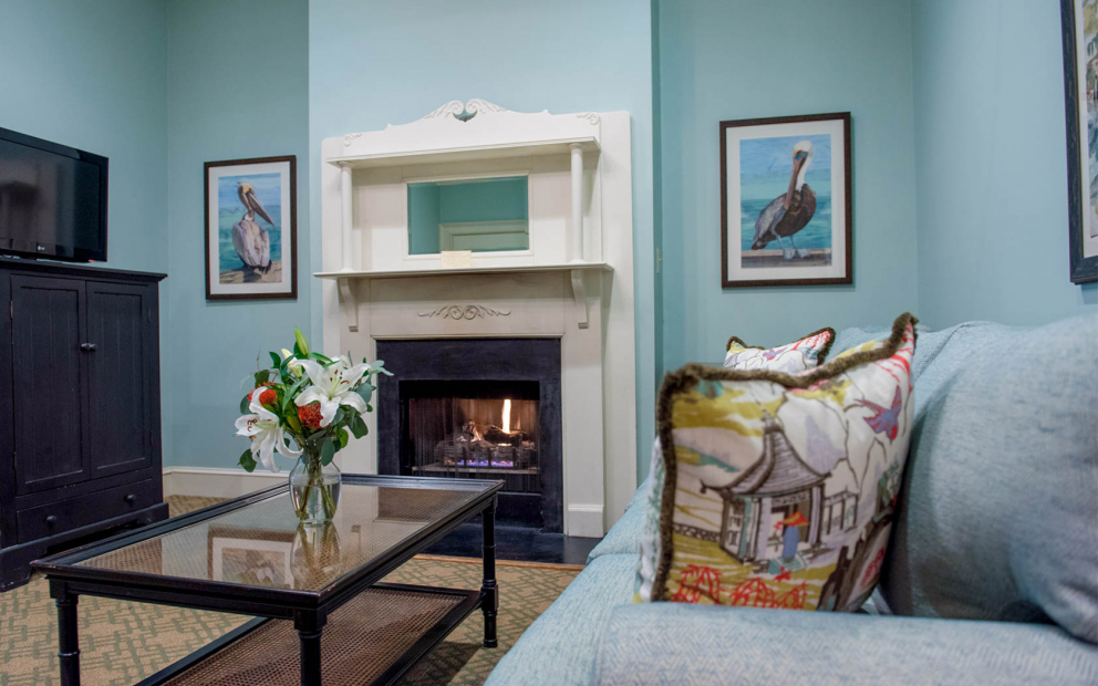 Room living space with light blue walls, white fireplace, blue sofa & glass coffee table