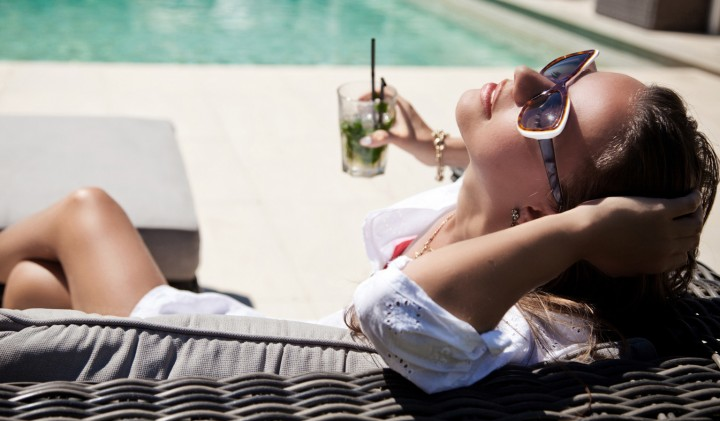 young fashionable woman on a pool lounge chair with a drink