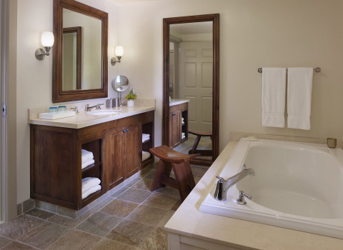 bathroom of a guestroom with a jacuzzi tub and double vanity