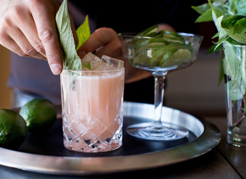 a pink frothy cocktail on a bar tray surrounded by limes and a bartender adding mint