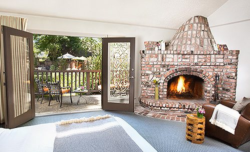 Room with brick fireplace and metallic seating on patio