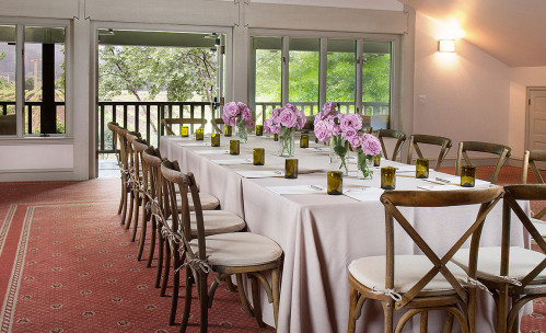 Long rectangular table with chairs & purple flower arrangements