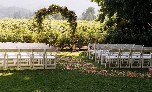 chairs set up with an isle outside for a wedding ceremony