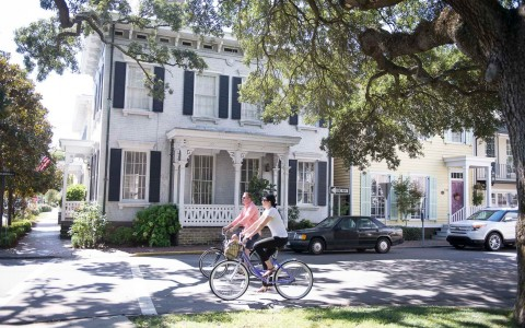 people biking in front of historic colonial home