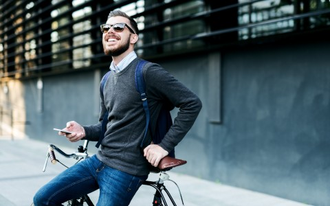 man leaning on bike holding phone