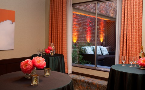 Hotel Triton reception space set with black tablecloths and pink flowers