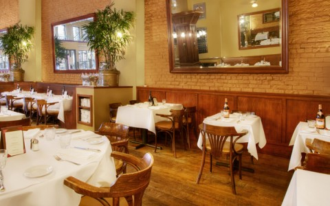 cafe tables in a classic restaurant with brick walls and white table cloths