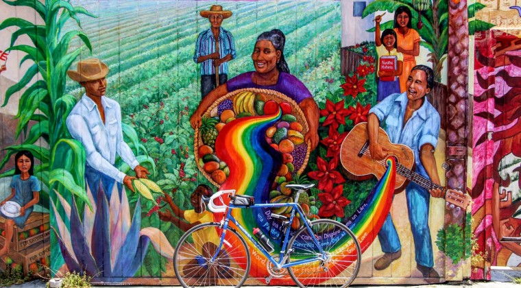 a bicycle parked in front of a colorful painted mural of farmers in the mission district