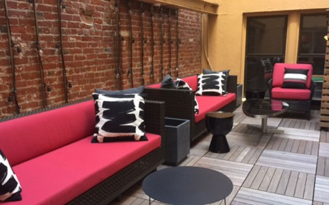 outdoor patio setting with red couches, black pillows and black tables