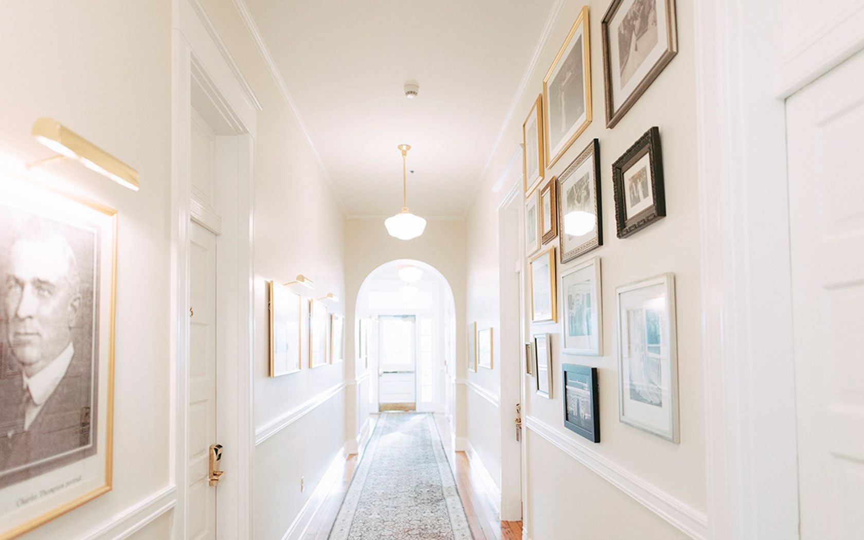 White hallway in hotel with frames hung