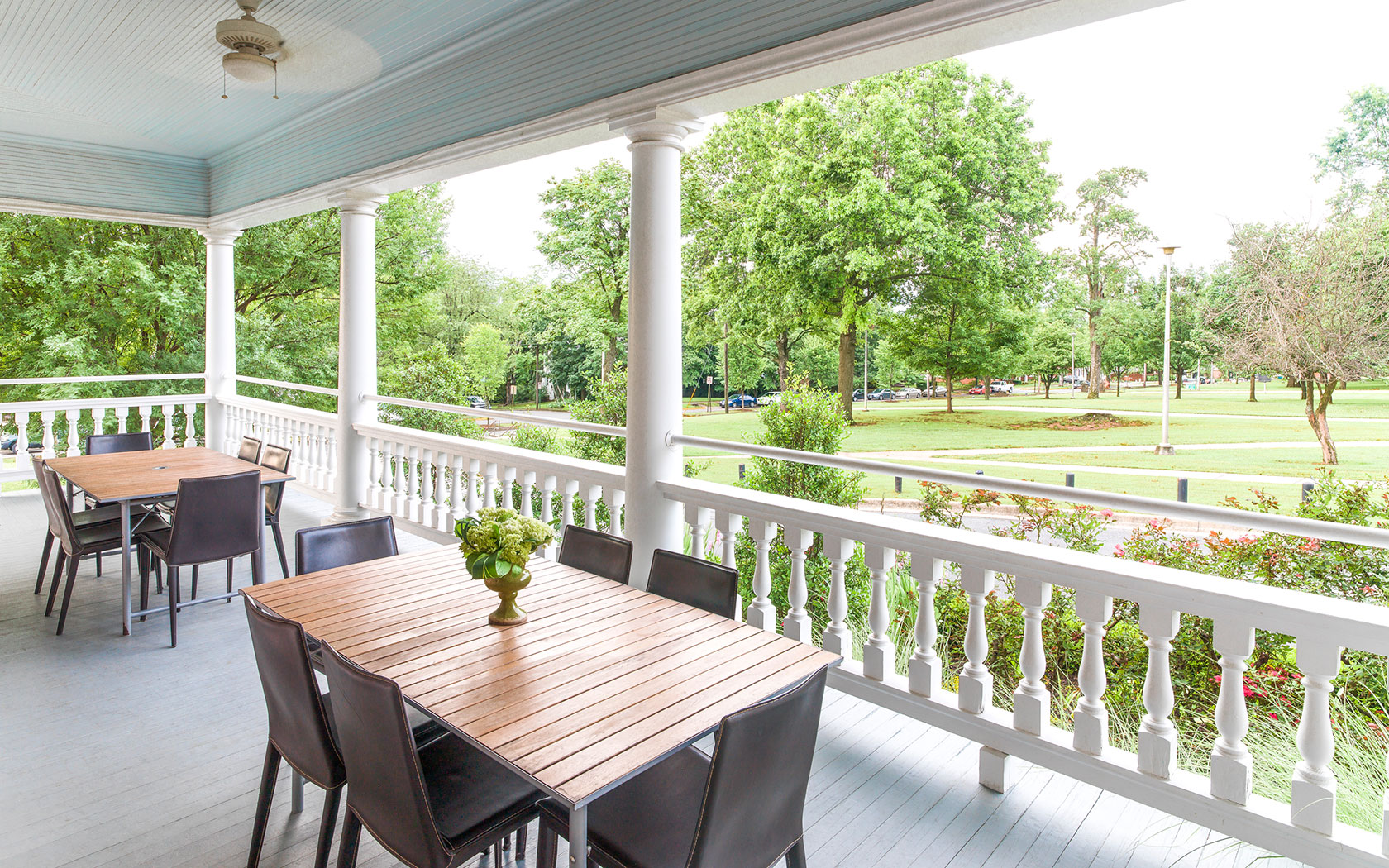 brown wooden tables on the southern style porch overlooking greenery