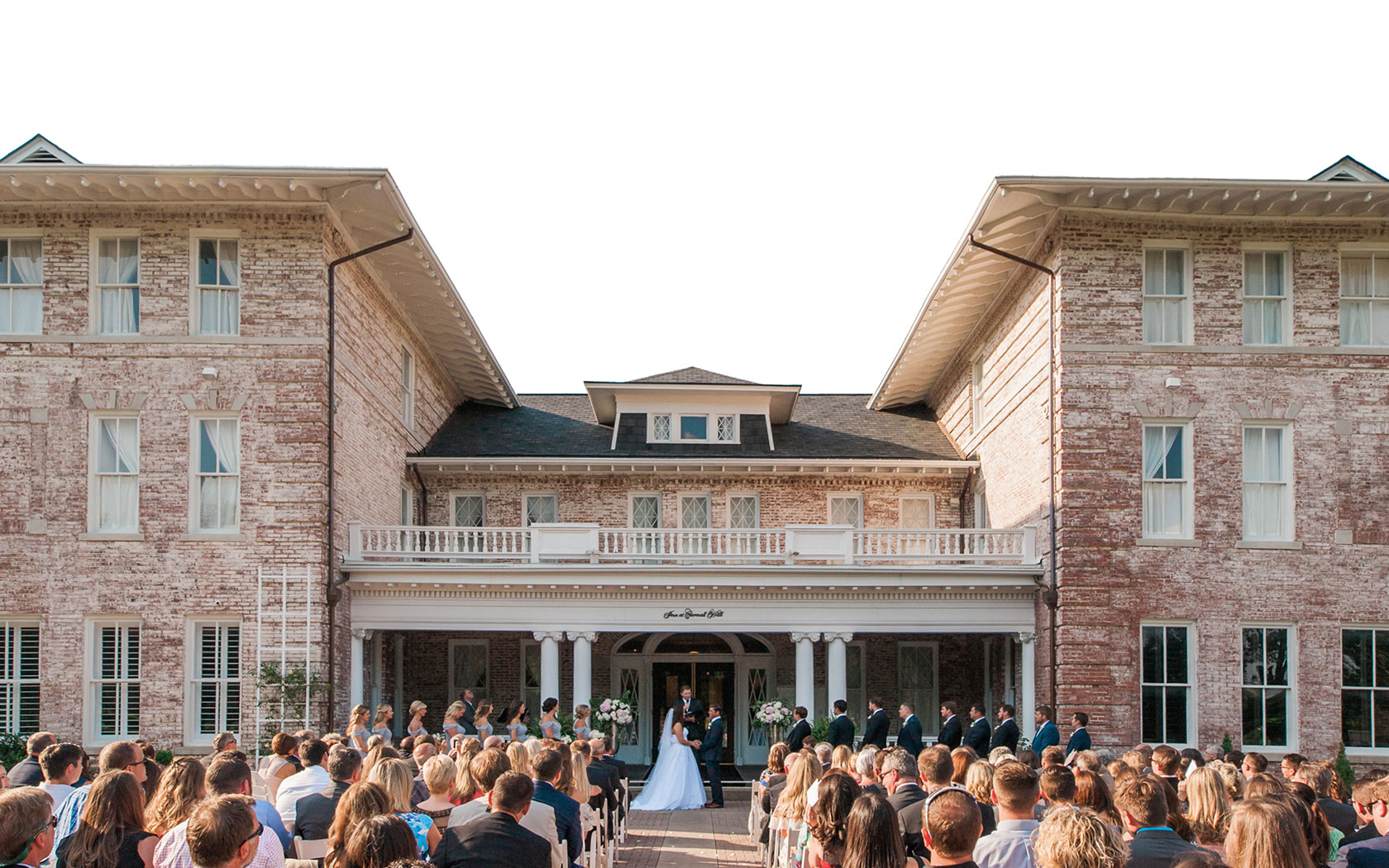 large outdoor wedding on the steps of the front of the hotel