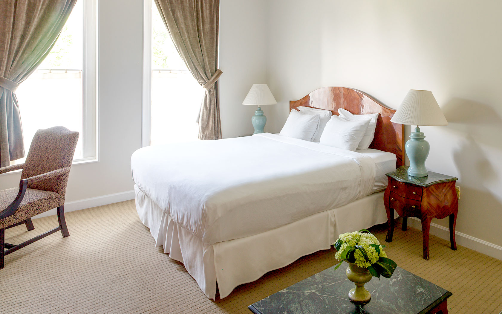 double bed with white linens and vintage furniture