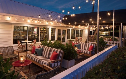 patio at night with lights hanging and cozy love seats