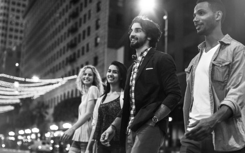 Black & white image of 4 friends walking down a street