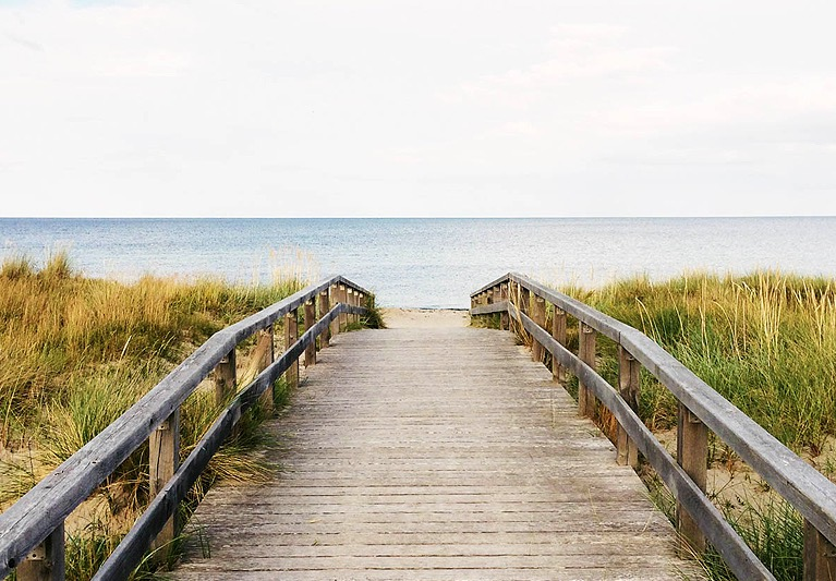 Wooden bridge leading to beach waters