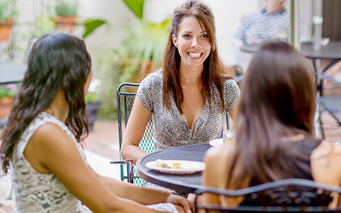 Three women sitting at outdoor terrace table during meal
