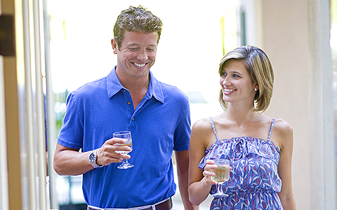 Couple walking back inside with glasses of white wine in hand